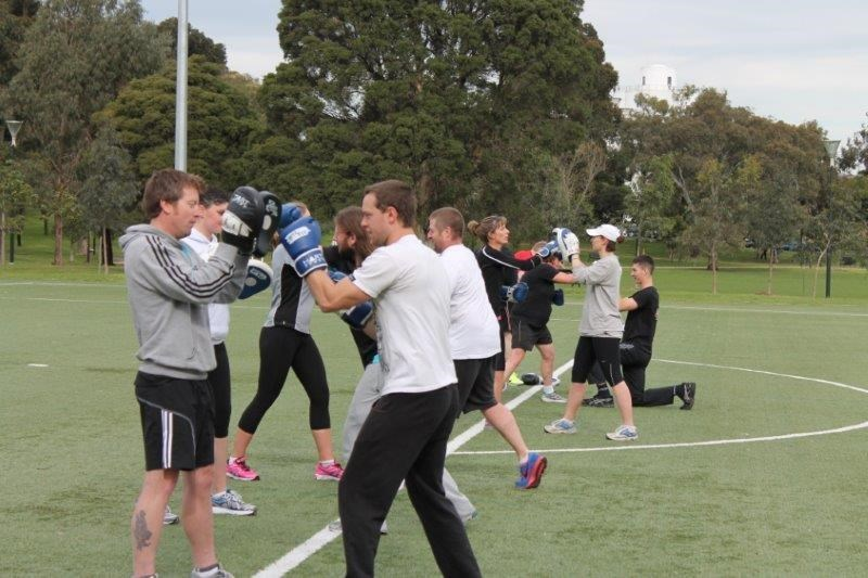 Sports team doing group boxing training session in sports field