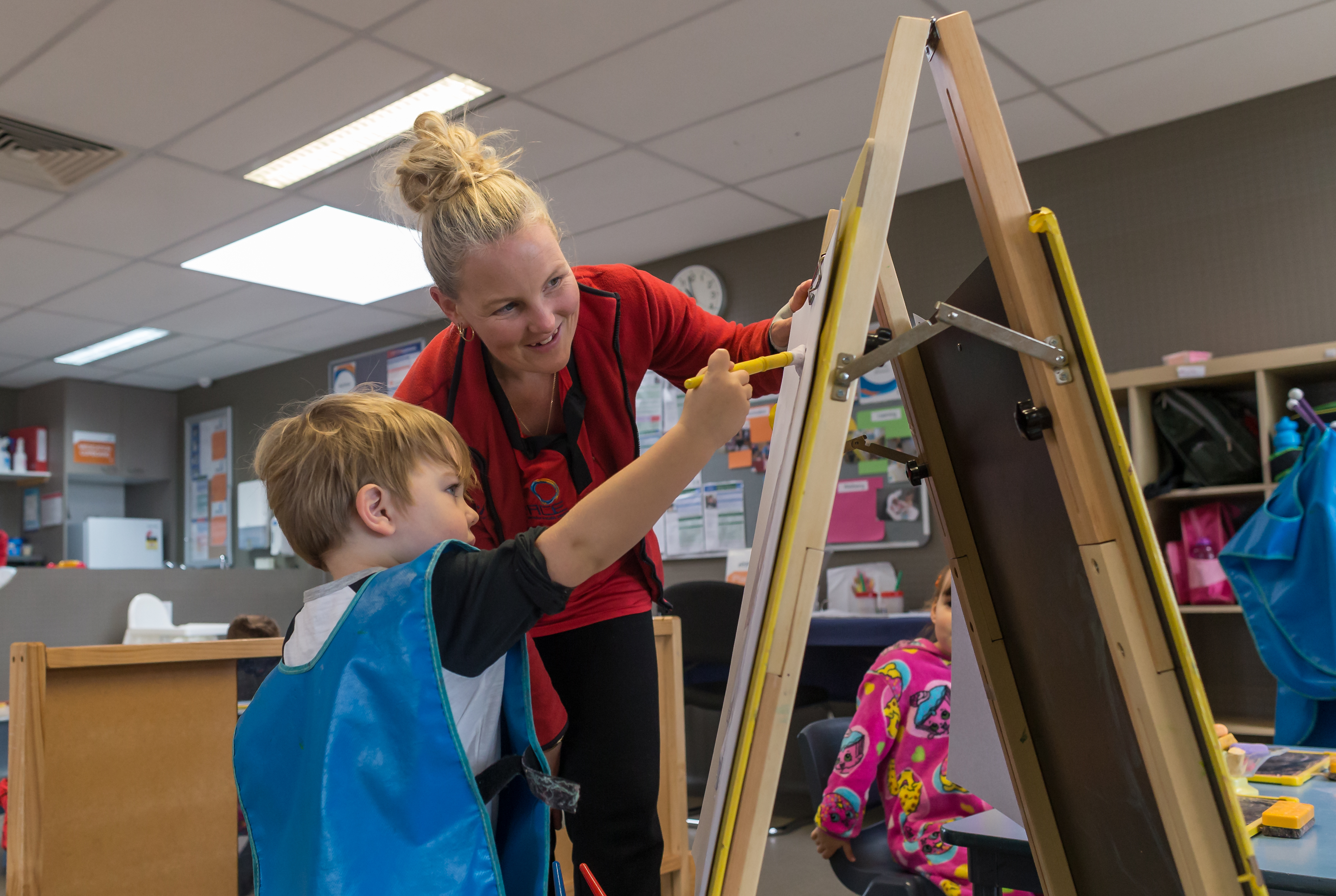Young boy doing art on an easel
