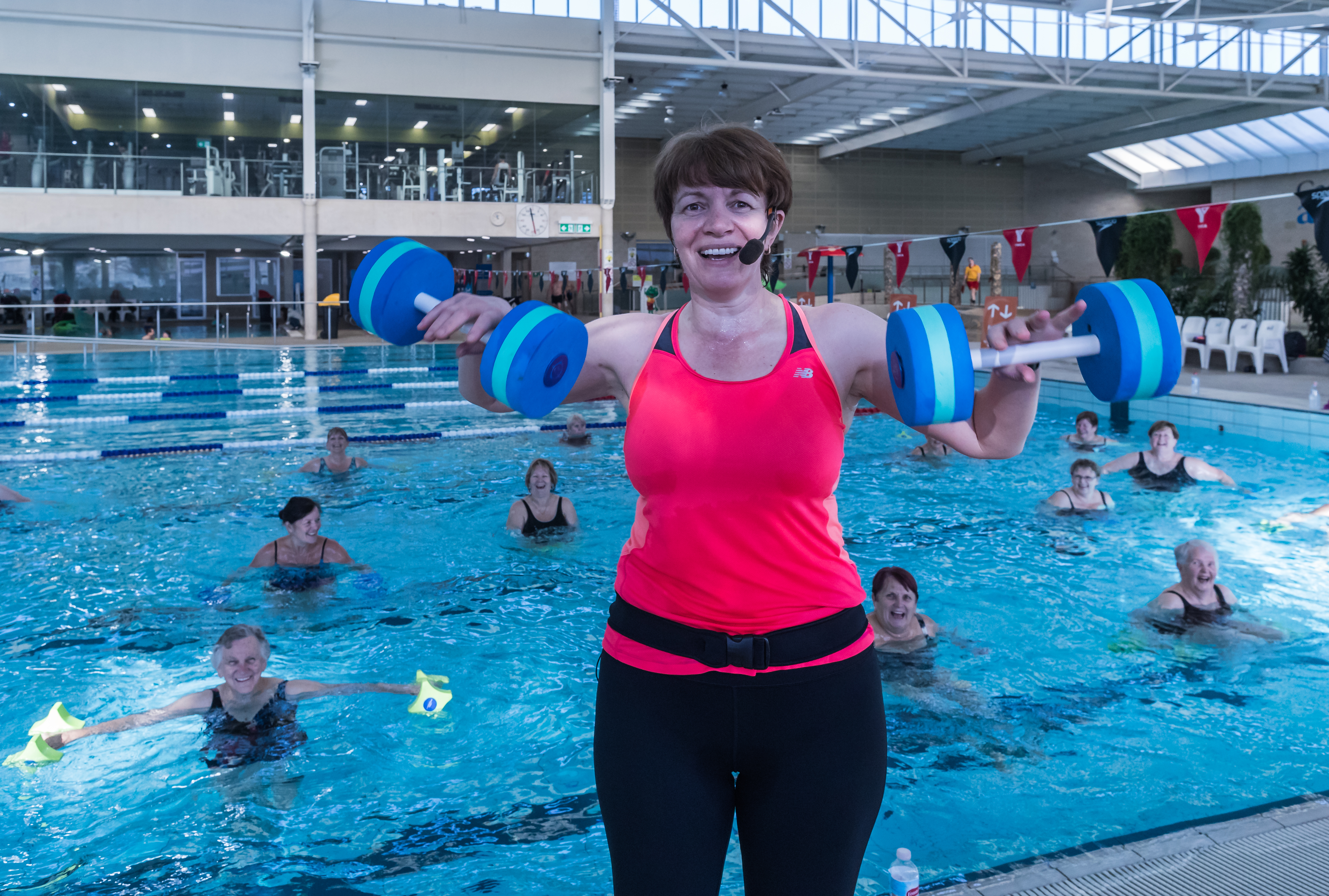 Aqua aerobics instructor demonstrating exercise in front of class