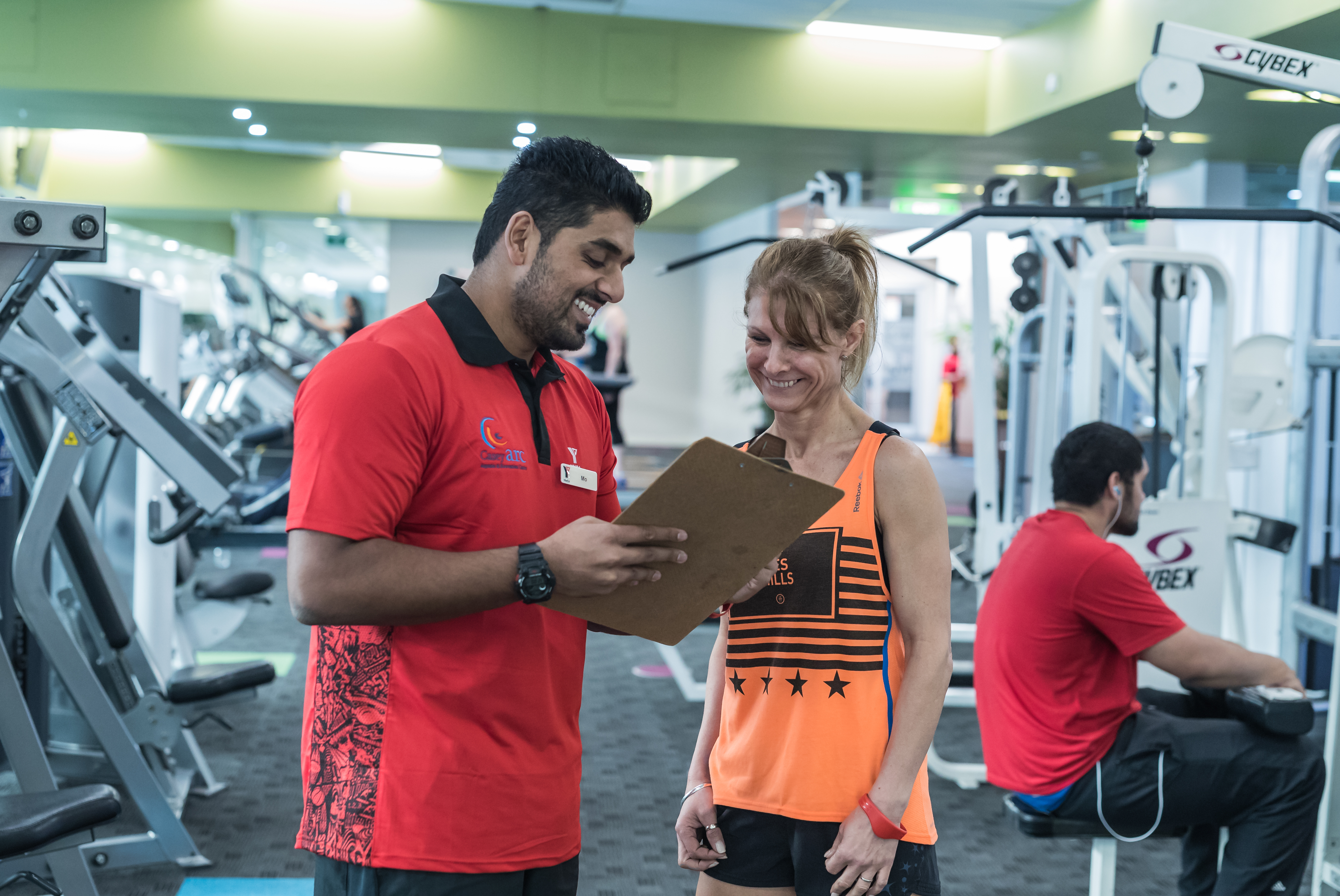 Woman with trainer looking at fitness goals on clipboard