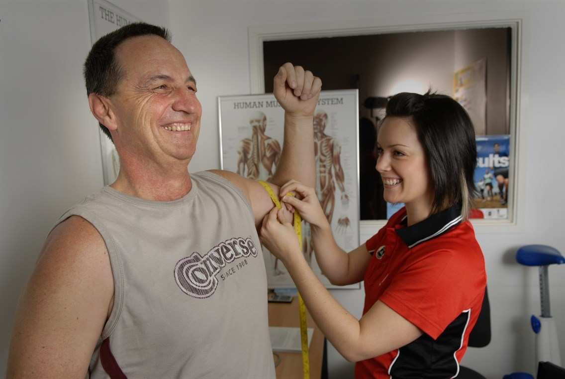 Man getting arm muscles measured by personal trainer