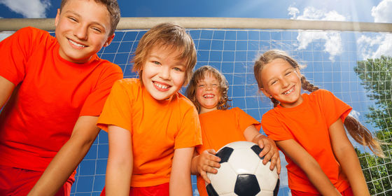 Kids In Orange Shirts Standing In Front Of Soccer Goals