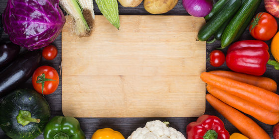 Fruits and vegetables surrounding a chopping board for healthy eating