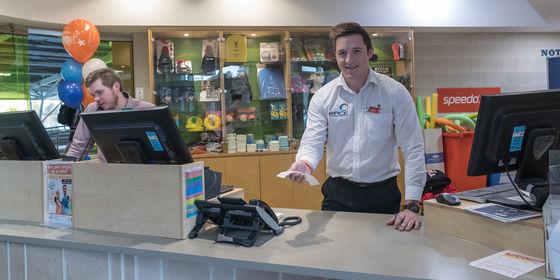 Man at front desk serving people