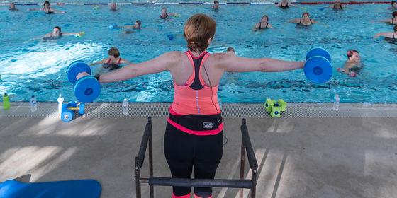 Aqua aerobics instructor standing in front of pool