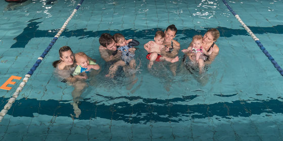 Parents swimming with kids