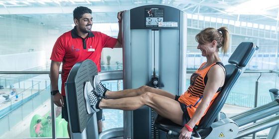 Woman using gym equipment with instructor